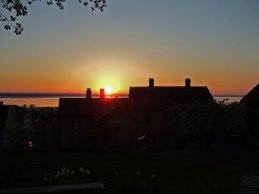 Solnedgång mellan husets skorstenar