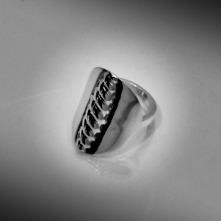 """Giksasuormas är en generös silverring med modernt formspråk, inspirerad av den traditionella samiska """"Larvenknappen"""", en bältesknapp med flätat mönster. Ställbar silverring från Jokkmokks Tenn."""