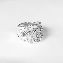 Kärleksringen är gjord av silver med ringar framtill och ett hjärta på varje sida. Den är reglerbar.