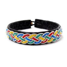 Handgjort tennarmband av svart naturgarvat renskinn och med fläta av tenntråd och läder i de samiska färgerna gult, rött, blått och grönt. Ca 1 cm bred och finns i längderna 15 cm - 22 cm.